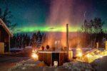 Feuertonnen mit Polarlichtern in Schweden